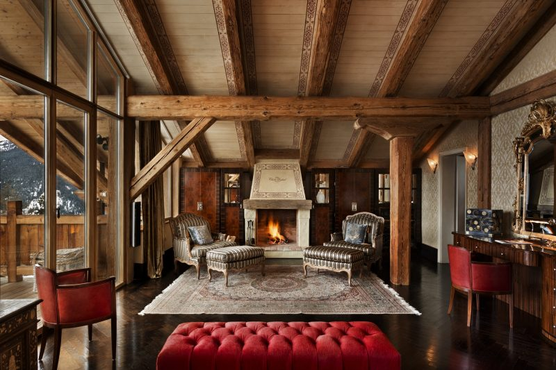 Switzerland's Best Ski Chalet nominee: The lush master bedroom provides incredible private space. Two lounging chairs sit alongside the bedroom's private fireplace