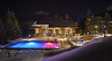 Luxury chalet Alpaca at night with outdoor swimming pool