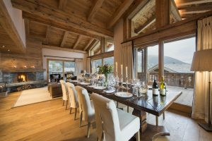 Switzerland's Best Ski Chalet nominee. Dining room table set up for dinner. Large windows take in the extraordinary views over the mountains