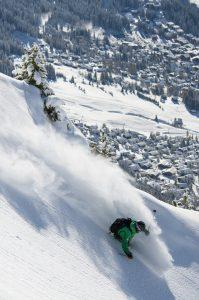 Skier kicking up fresh powder over Verbier