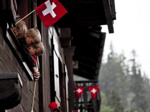 Children looking out the window with a Swiss flag