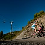 Cyclists with ski lifts overhead