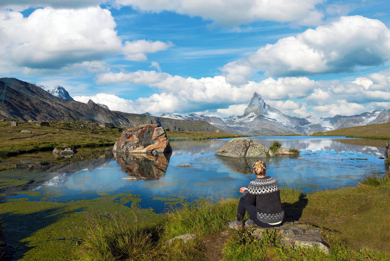 Girl tourist looks at the Matterhorn and Lake Stellisee in the Swiss Alps, near Zermatt, Switzerland, Europe