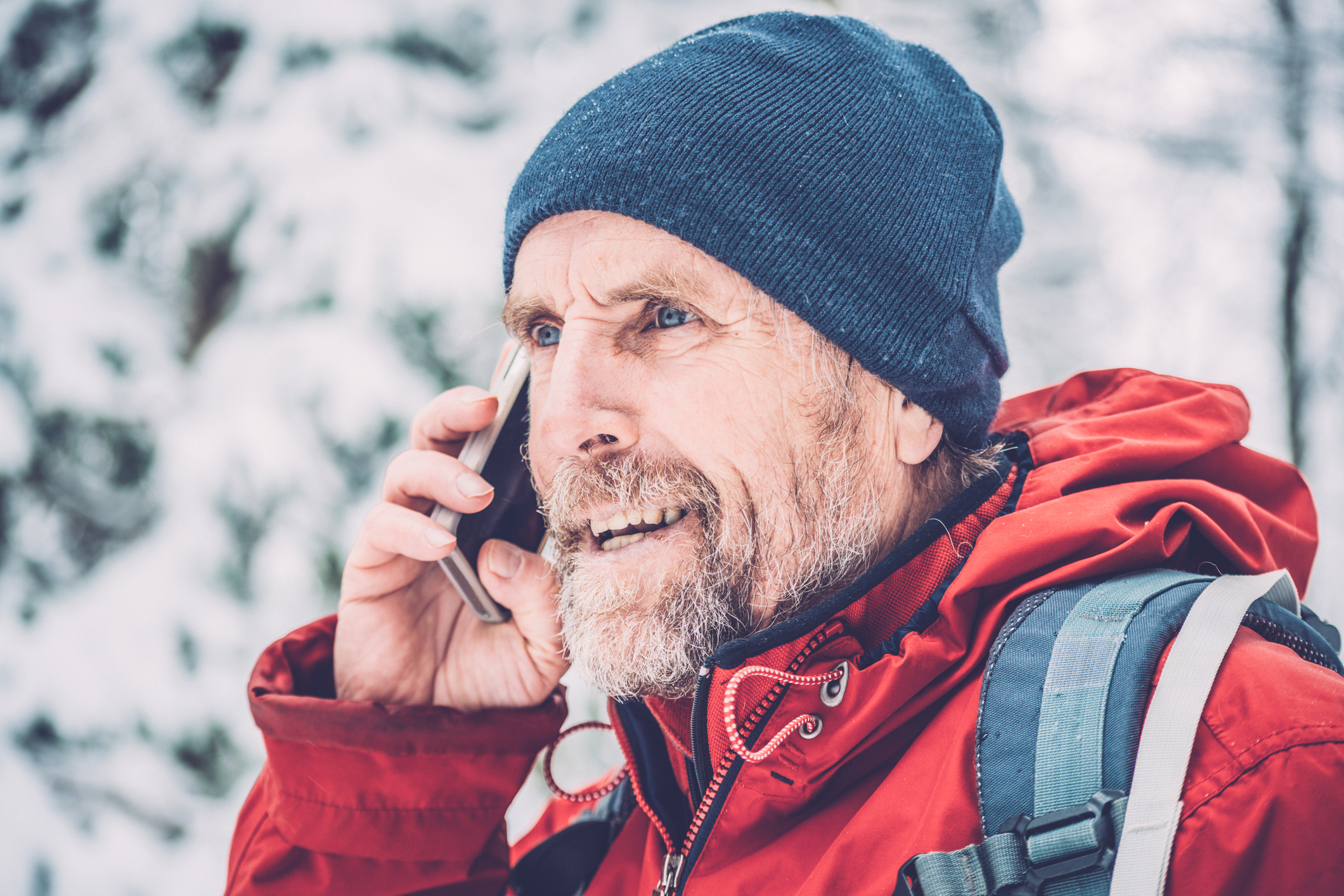 Portrait of a happy senior man on a phone while hiking in the forest